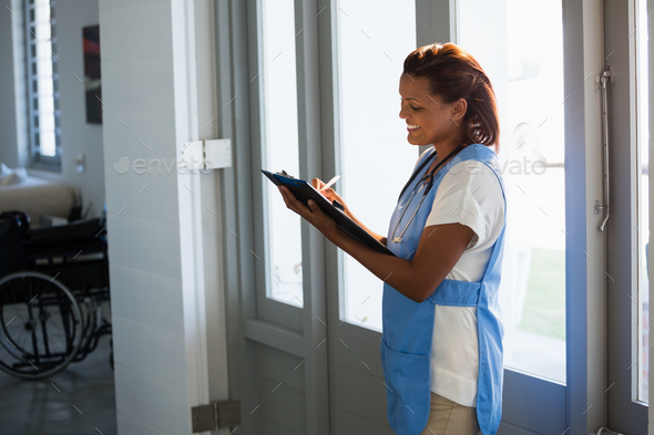 Doctor writing on clipboard in the hospital - Stock Photo - Images