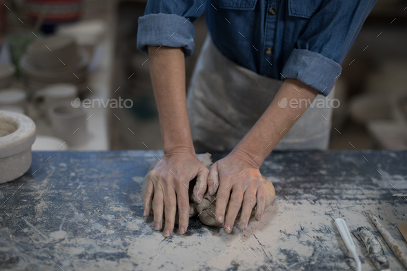 Mid section of female potter molding a clay - Stock Photo - Images