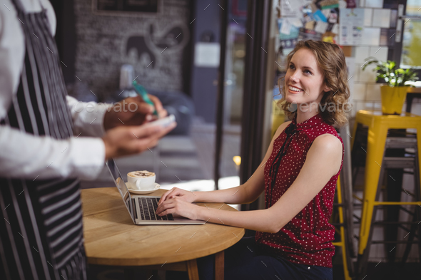 Midsection of waiter holding notepad while standing by smiling young female customer - Stock Photo - Images