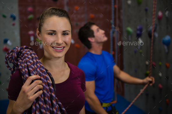 Athlete carrying rope while trainer climbing wall at gym - Stock Photo - Images