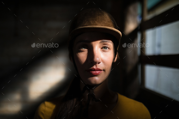 Confident female jockey in stable - Stock Photo - Images