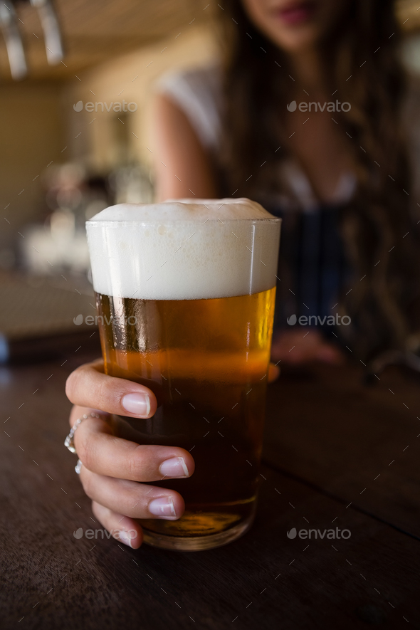 Close-up of barmaid holding beer glass - Stock Photo - Images
