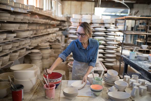 Female potter painting bowl - Stock Photo - Images