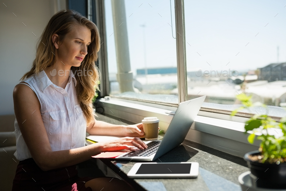 Young businesswoman working while using laptop - Stock Photo - Images