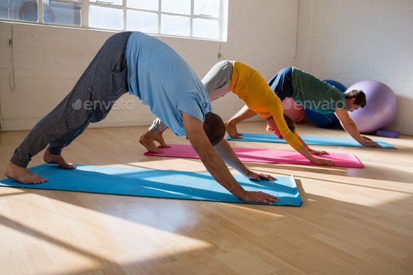 instructor with students practicing downward facing dog pose in yoga studio - Stock Photo - Images