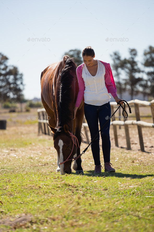 Full length of woman standing with horse - Stock Photo - Images