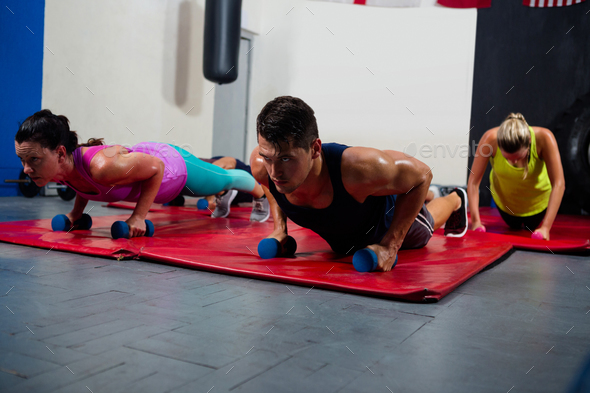 Young male and female athletes practicing push ups on dumbbells - Stock Photo - Images