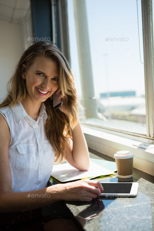 Portrait of smiling businesswoman talking on mobile phone - Stock Photo - Images