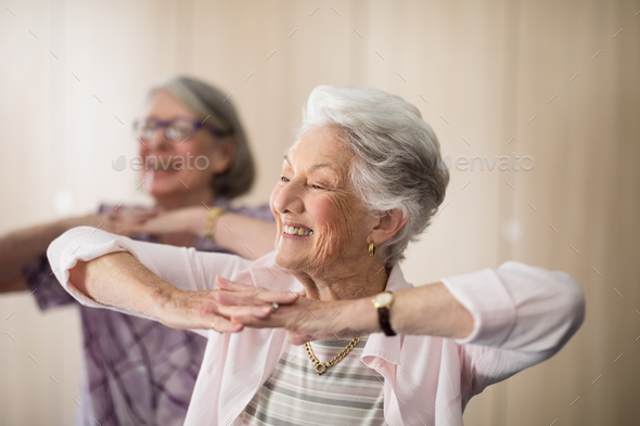 Smiling senior women with hands clasped looking away - Stock Photo - Images