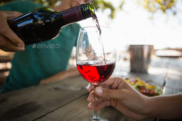 Man pouring wine in glass held by female friend - Stock Photo - Images