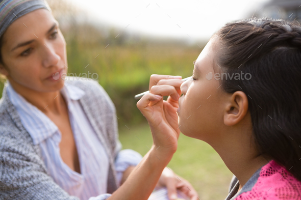 Close up of woman applying face paint - Stock Photo - Images