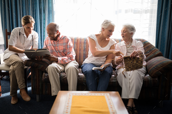 Female doctor reading book with man while senior women talking against window - Stock Photo - Images