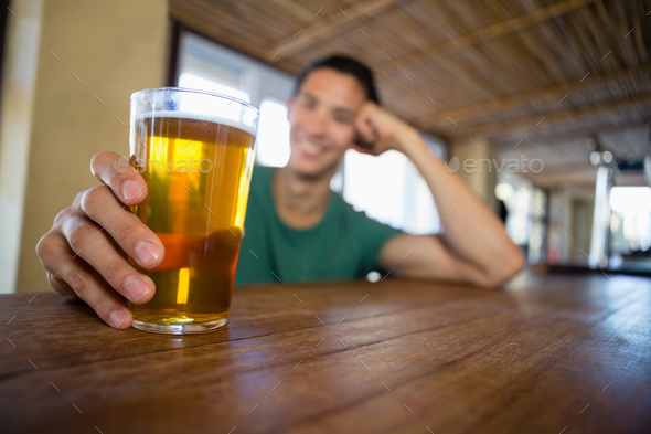 Man holding beer glass at bar counter - Stock Photo - Images