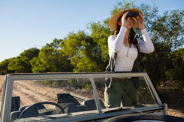 Young woman looking through binoculars standing in off road vehicle - Stock Photo - Images