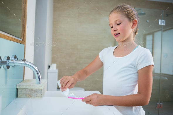 Girl removing toothpaste on brush - Stock Photo - Images