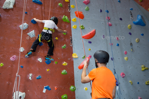 Trainer assisting boy in rock climbing - Stock Photo - Images