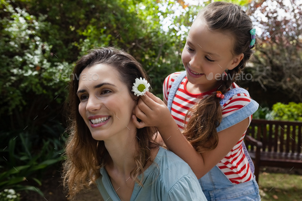 Girl positioning white flower in hair of mother - Stock Photo - Images