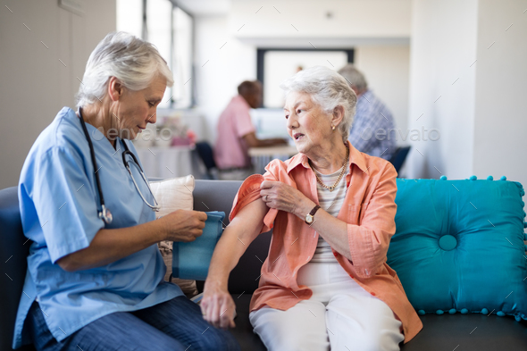 Female doctor checking blood pressure of senior woman - Stock Photo - Images