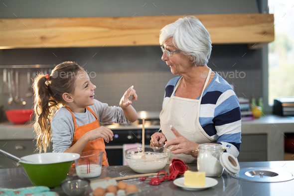 Granddaughter putting flour on grandmothers nose - Stock Photo - Images