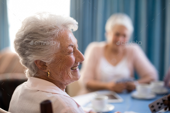 Happy senior woman sitting with friends - Stock Photo - Images