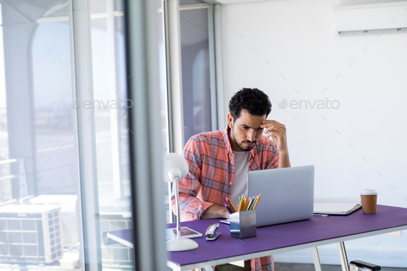 Male executive working over laptop - Stock Photo - Images