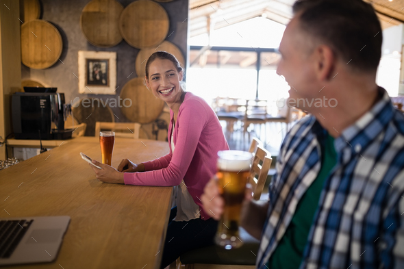 Friends interacting with each other while having glass of beer - Stock Photo - Images