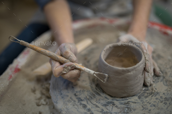 Female potter molding plate with hand tool - Stock Photo - Images