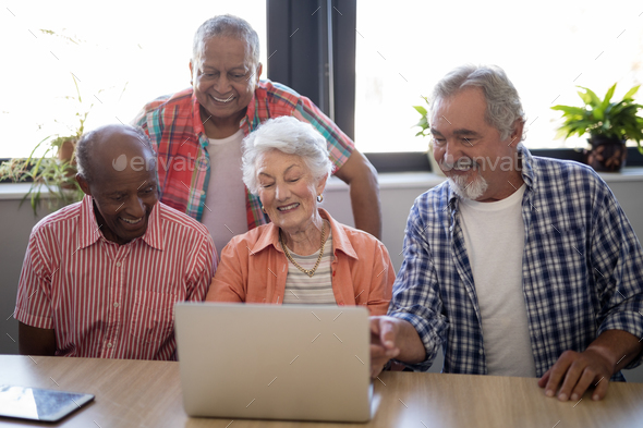 Happy senior people using laptop at table - Stock Photo - Images