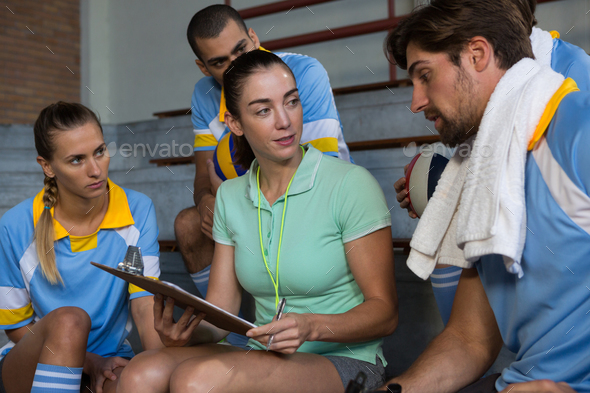 Coach having discussion with volleyball players - Stock Photo - Images