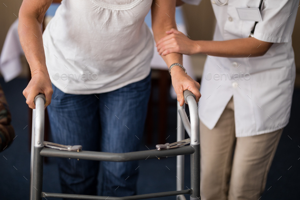 Midsection of female doctor assisting senior woman walking with walker - Stock Photo - Images