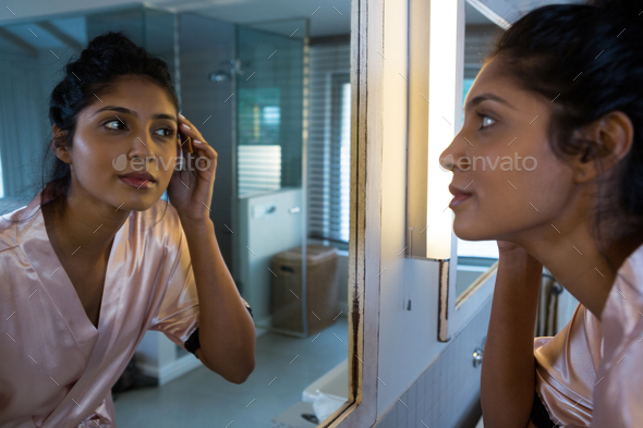 Woman reflecting on mirror in bathroom - Stock Photo - Images