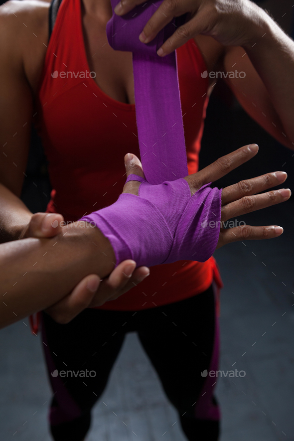 Trainer tying hand wrap on woman hand - Stock Photo - Images