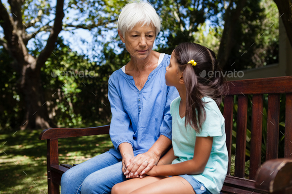 Grandmother and granddaughter holding hands while sitting on bench - Stock Photo - Images