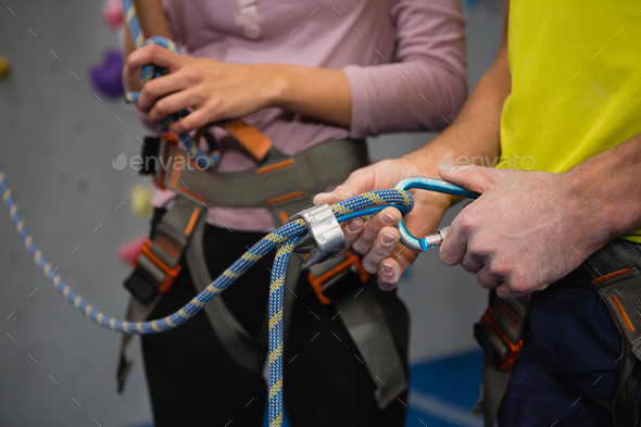 Midsection of athletes adjusting safety harness in club - Stock Photo - Images