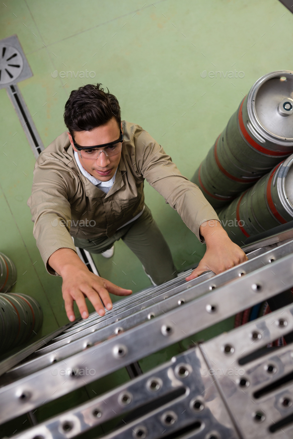 High angle view of worker climbing ladder at brewery - Stock Photo - Images