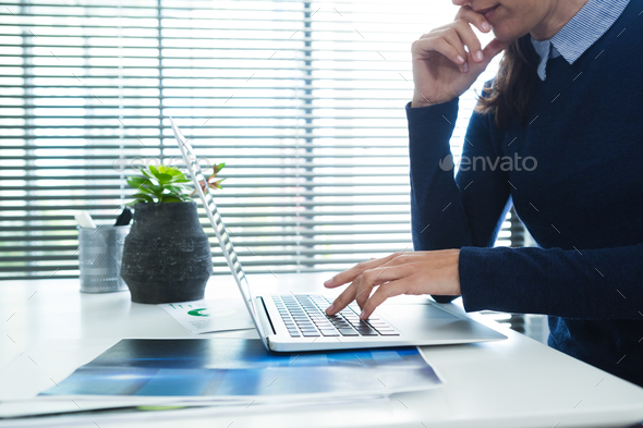Female executive using laptop at desk - Stock Photo - Images