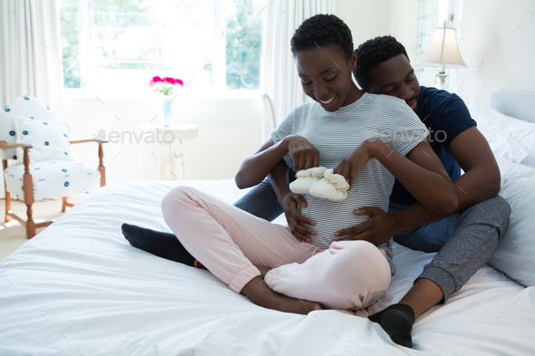 Couple holding baby socks in bedroom - Stock Photo - Images