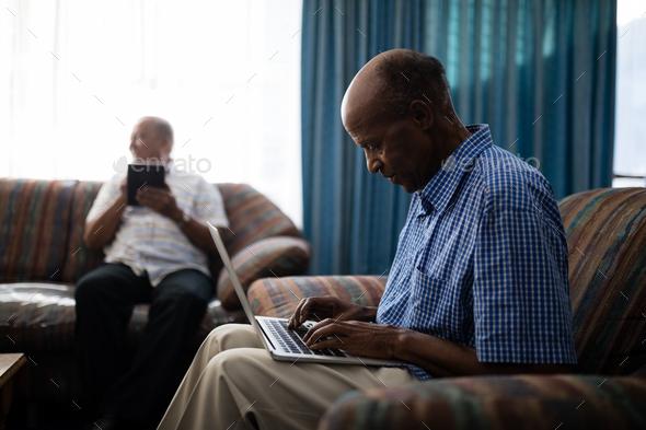Senior man using laptop while sitting on sofa - Stock Photo - Images