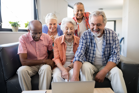 Cheerful senior friends looking at laptop on table - Stock Photo - Images