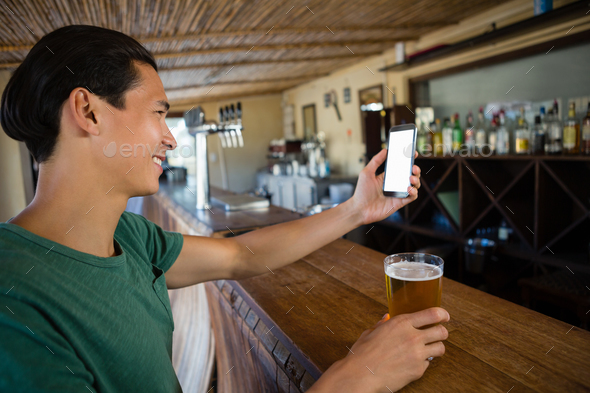 Smiling man taking selfie while having beer at bar - Stock Photo - Images