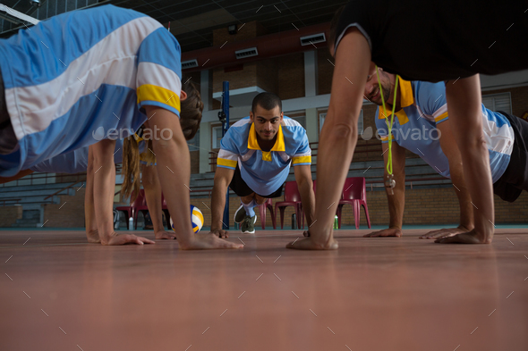 Volleyball players doing push-ups with coach - Stock Photo - Images