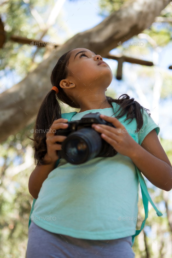 Little Girl With Backpack Holding Dslr Camera In Her Hand Looking Up In The Sky On A Sunny Day Stock Photo By Wavebreakmedia