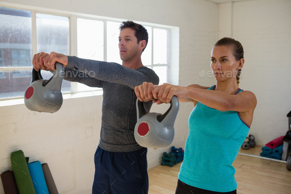Confident athletes lifting kettlebells - Stock Photo - Images