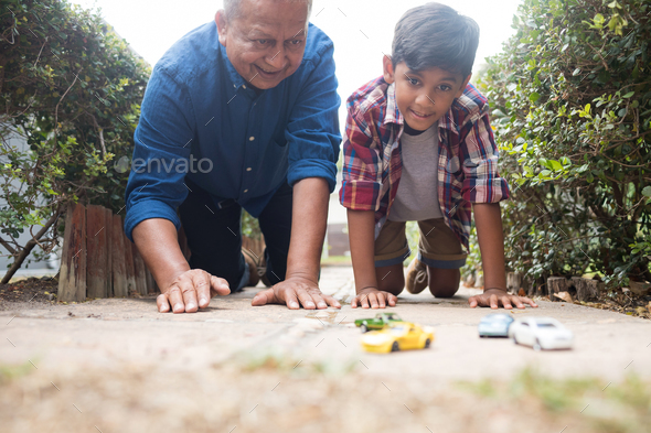 Boy and grandfather playing with toy cars - Stock Photo - Images