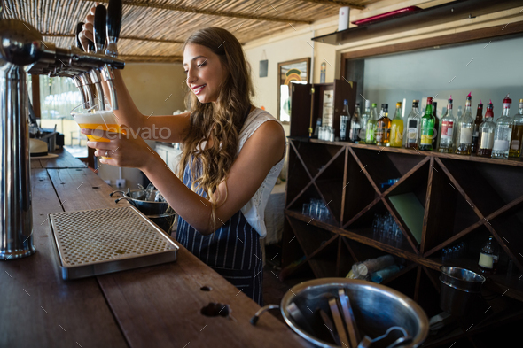 Barmaid pouring beer from tap in glass at bar - Stock Photo - Images