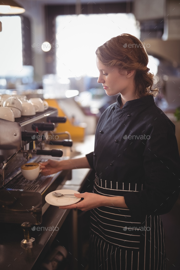 Young waitress making coffee from espresso maker - Stock Photo - Images