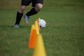 Soccer player dribbling through cones - PhotoDune Item for Sale