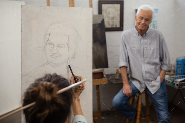 Senior man watching while artist drawing on canvas - Stock Photo - Images