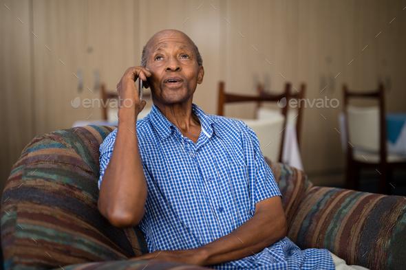 Senior man talking on mobile phone while sitting on sofa - Stock Photo - Images