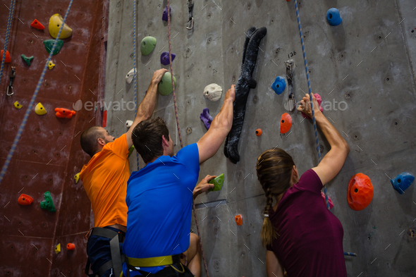 Athletes and trainer climbing wall in gym - Stock Photo - Images